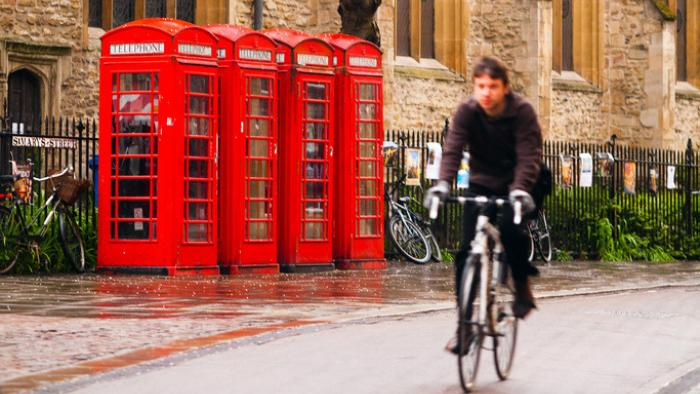 Cyclist riding past telephone boxes by James Appleton/Unsplash