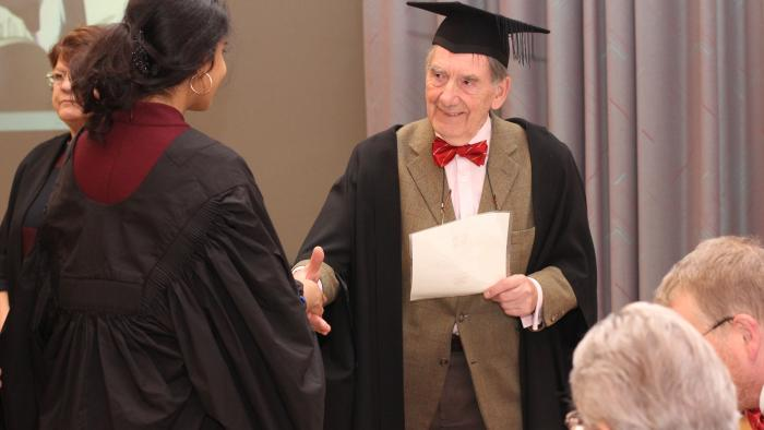 Praelector greeting new undergraduate at matriculation