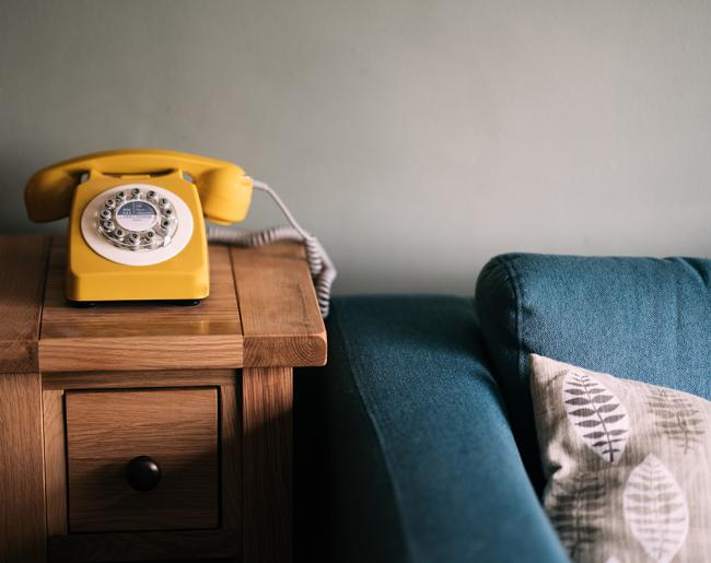 Rotary telephone by a sofa