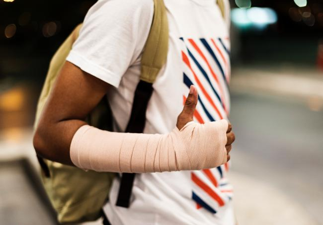 Man with bandage and thumbs up sign