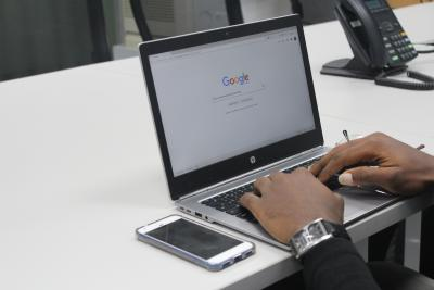 hands typing into Google on a laptop
