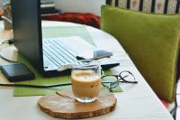 A macbook, cup of coffee, glasses on a table